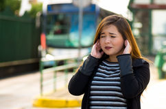 Pretty young woman covering her ears with both hands on the street in the city with sound pollution with a blurred bus Royalty Free Stock Photos