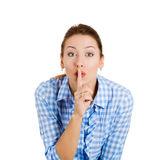 Pretty young woman covering her lips with finger Stock Image