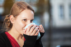 Pretty young woman with cup of chocomilk. Pretty young woman drinking hot drink from a ceramic cup outdoors Stock Photos