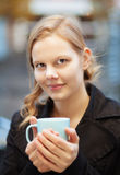 Pretty young woman with cup of chocomilk. Pretty young woman holding a cup of hot drink outdoors Royalty Free Stock Photo