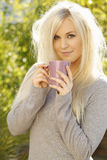 Pretty young woman with a cup of coffee outside. Pretty young woman holds a cup of coffee in her hands in front of a natural background stock image