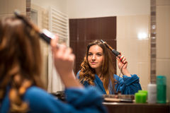 Pretty, young woman curling her hair in front of her bathroom Royalty Free Stock Images