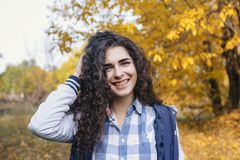 Woman with curly black hair and smiling face standing in autumn park Royalty Free Stock Image