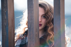 Pretty young woman with curly hair behind of a wooden columns Stock Images