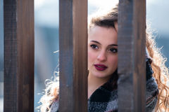 Pretty young woman with curly hair behind of a wooden columns Stock Photos