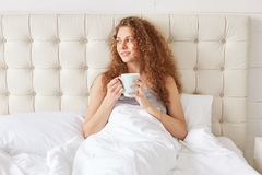 Pretty young woman with curly hair has morning aromatic coffee i. N bed, looks pleasantly away, enjoys sunrise, has good relax in bedroom. Relaxed adorable Royalty Free Stock Images