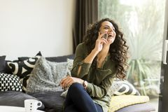 Pretty young woman with mobile phone in the room stock photography