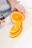 Pretty young woman cut orange. Isolated Royalty Free Stock Image