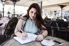 Pretty young woman with dark long hair and blue eyes sits in caf. E and drinks turkish coffee and write something in the notebook,  on the harbour in a small Royalty Free Stock Photo