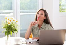 Woman daydreaming at office desk. Pretty young woman daydreaming in front of laptop. Sitting at table in big sunny room with flowers Stock Image
