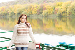 Pretty young woman on a deck above a river Royalty Free Stock Images