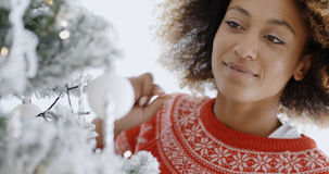 Pretty young woman decorating a Christmas tree Royalty Free Stock Photos