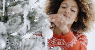 Pretty young woman decorating a Christmas tree Royalty Free Stock Photo