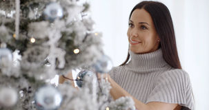 Pretty young woman decorating her Christmas tree Royalty Free Stock Photography