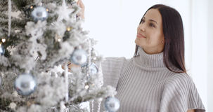 Pretty young woman decorating her Christmas tree Royalty Free Stock Photos