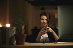 Pretty young woman designer sitting indoors chatting by phone Stock Images