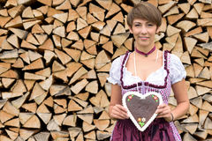 Pretty young woman in a dirndl holding a heart. Pretty young Bavarian woman in a traditional dirndl holding a heart shaped biscuit or cake with decorative icing royalty free stock photography