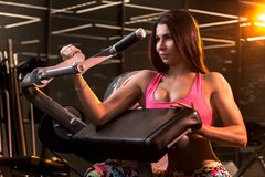 Pretty young woman is doing bicep curls in the training apparatus at the gym royalty free stock image