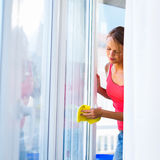 Pretty, young woman doing house work - washing windows. (shallow DOF; color toned image royalty free stock photo