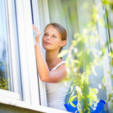 Pretty, young woman doing house work - washing windows. (shallow DOF; color toned image royalty free stock images