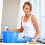 Pretty, young woman doing house work - washing windows Royalty Free Stock Photos
