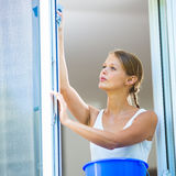Pretty, young woman doing house work - washing windows. (shallow DOF; color toned image royalty free stock photography