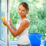 Pretty, young woman doing house work - washing windows. (shallow DOF; color toned image stock photos