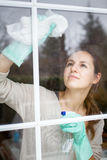 Pretty, young woman doing house work - washing windows Royalty Free Stock Images