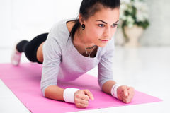 Pretty young woman doing plank abdominal exercise. At home in white room royalty free stock image