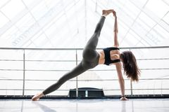 Pretty young woman doing YOGA exercise in big fitness hall. Young woman doing YOGA exercise in big fitness hall Royalty Free Stock Photo