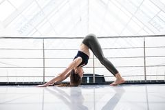 Pretty young woman doing YOGA exercise in big fitness hall. Young woman doing YOGA exercise in big fitness hall Stock Photography