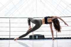 Pretty young woman doing YOGA exercise in big fitness hall Stock Images