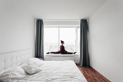 Pretty young woman doing yoga exercise at home on a window Royalty Free Stock Image