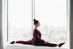 Pretty young woman doing yoga exercise at home on a window Stock Photos