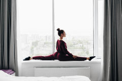 Pretty young woman doing yoga exercise at home on a window Stock Photo