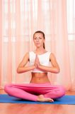 Pretty young woman doing yoga exercise on mat Stock Photo