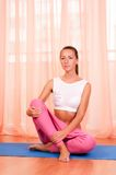 Pretty young woman doing yoga exercise on mat Stock Photography