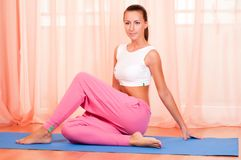 Pretty young woman doing yoga exercise on mat Stock Images
