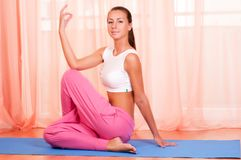 Pretty young woman doing yoga exercise on mat Royalty Free Stock Image