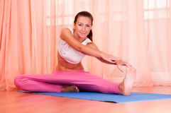 Pretty young woman doing yoga exercise on mat Stock Image