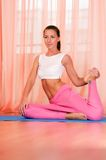 Pretty young woman doing yoga exercise on mat Stock Photos