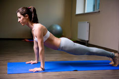 Pretty young woman doing yoga exercise. On mat Stock Images