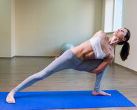 Pretty young woman doing yoga exercise. On mat Stock Photos