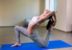 Pretty young woman doing yoga exercise. On mat Royalty Free Stock Image