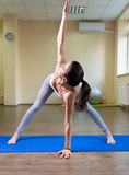 Pretty young woman doing yoga exercise. On mat Royalty Free Stock Photos