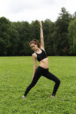 Pretty young woman doing yoga. Pretty young woman doing yoga exercises in the park Royalty Free Stock Photos