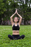Pretty young woman doing yoga. Pretty young woman doing yoga exercises in the park Stock Photos