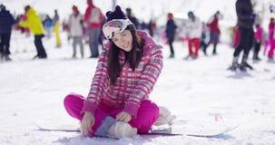 Woman sitting on snowboard stock video