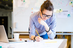 Pretty young woman drawing blueprint by pencil in the office. Pretty young woman in glasses using laptop and drawing blueprint by pencil in the office Stock Photo
