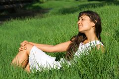 Pretty young woman dreaming on the grass Stock Photos